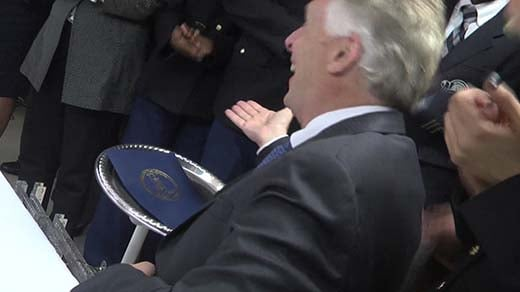 Gov. McAuliffe taking the bill from the robot
