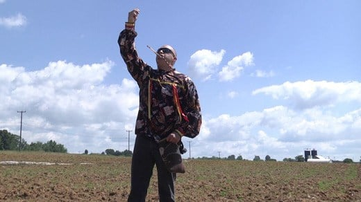Ponca Tribe member Mekasi Horinek praying over the planting of corn seeds in Augusta County.
