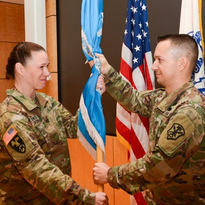 Col. Dana Rucinski, left, incoming commander National Ground Intelligence Center, passes the flag to Command Sgt. Maj. Jason H. Murray as keeper of the brigade colors (Photo courtesy U.S. Army Photographer Erich Ryland)