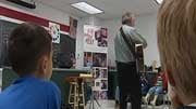 Students watch as Paul Reisler gathers song ideas from the crowd.