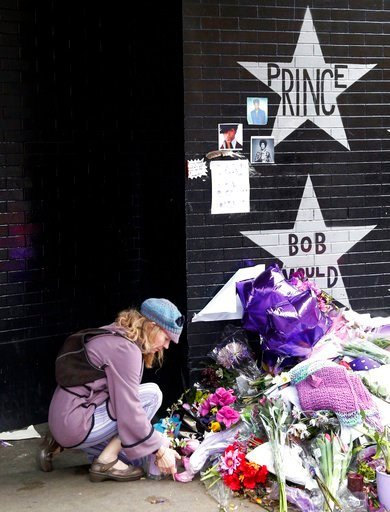 (AP Photo/Jim Mone, File). FILE - In this April 22, 2016 file photo, a woman places flowers at a memorial at First Avenue in Minneapolis where pop super star Prince often performed.