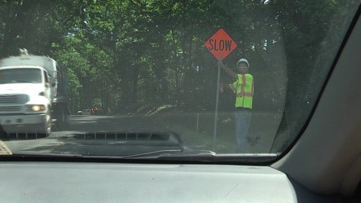 Worker alerting drivers to slowly drive through a work zone along Route 33