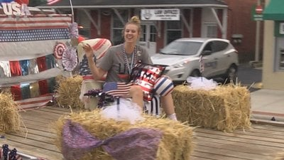 Sam Brunelle rides on a float down Main St.