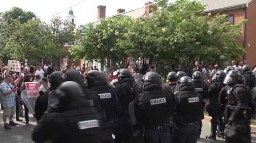 Officers in riot gear confront protesters in downtown Charlottesville