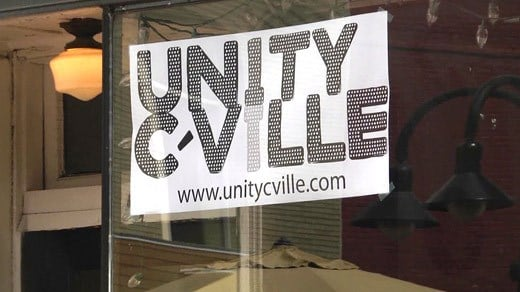 Sign for Unity Cville hanging in the window of a business on Charlottesville's Downtown Mall