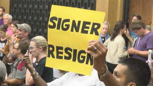 "Sign displayed at council meeting ""Signer Resign"""