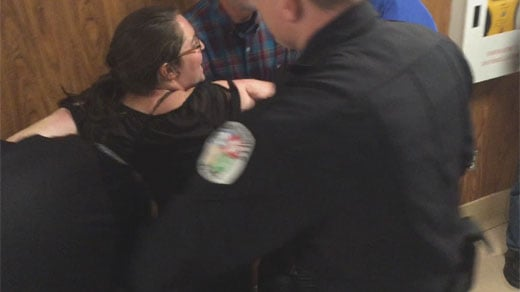 Woman being arrested at city council meeting