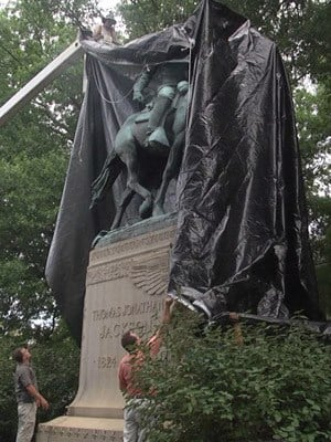 Crews covering the statue on August 23