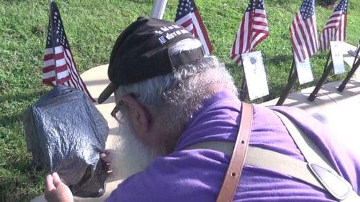 John Miska covering up Vietnam War plaques.