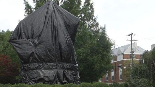 Tarp covering a Confederate statue