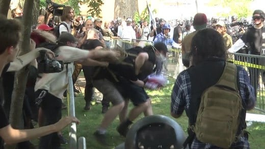 People look on as a fight breaks out at the Unite the Right rally (FILE IMAGE)
