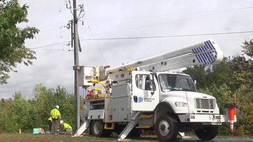 Crews working on a power pole damaged from a storm