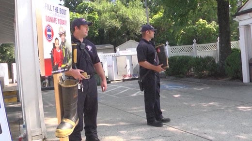 Firefighters are working to fill up a boot with donations