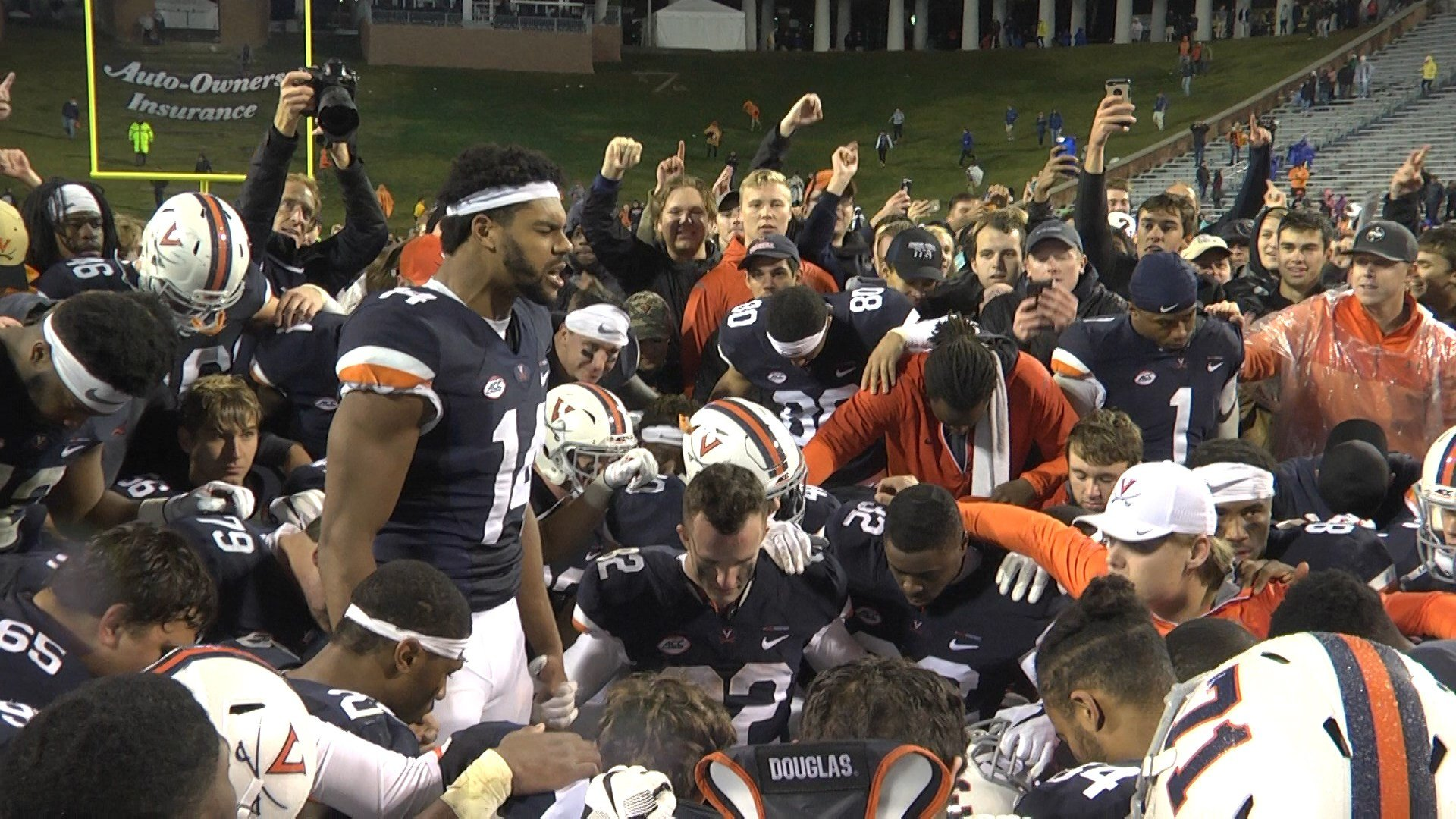 Andre Levrone talks to his teammates following the 'Hoos 40-36 victory