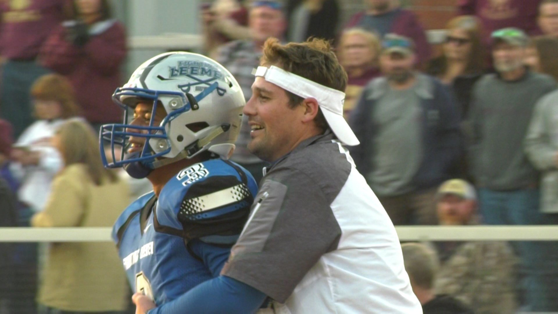 Head coach Scott Girolmo hugs senior QB Jayden Williams