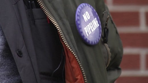 """A """"NO PIPELINE"""" button on Quinn Robinson's jacket"""