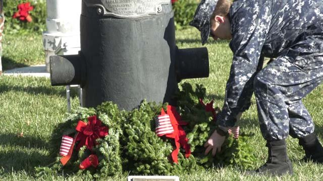 A volunteer places a wreath on a gravesite