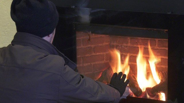 Person warms by a fireplace at the Haven in Charlottesville
