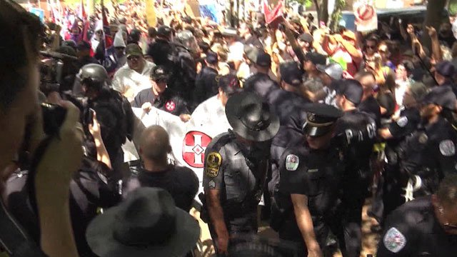 Law enforcement officers escorting supporters and members of the Loyal White Knights of the KKK for a rally at Charlottesville's Justice Park (FILE IMAGE)