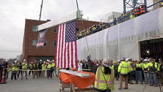 Construction crews gathered for the topping off ceremony