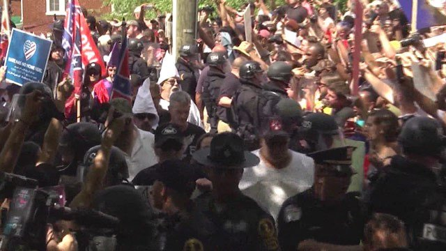 Authorities escorting supporters and members of a KKK group past protesters into Justice Park (FILE IMAGE)
