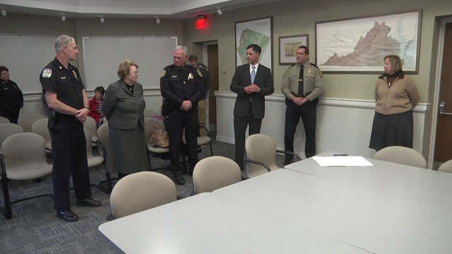 Tracci, Sullivan, and police and community representatives  sign agreement