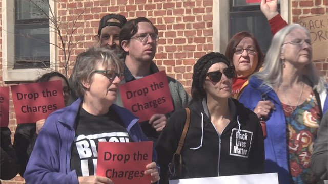 "Protesters display ""drop the charges"" signs"