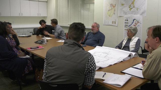 Folks discussing plans for development along East High Street