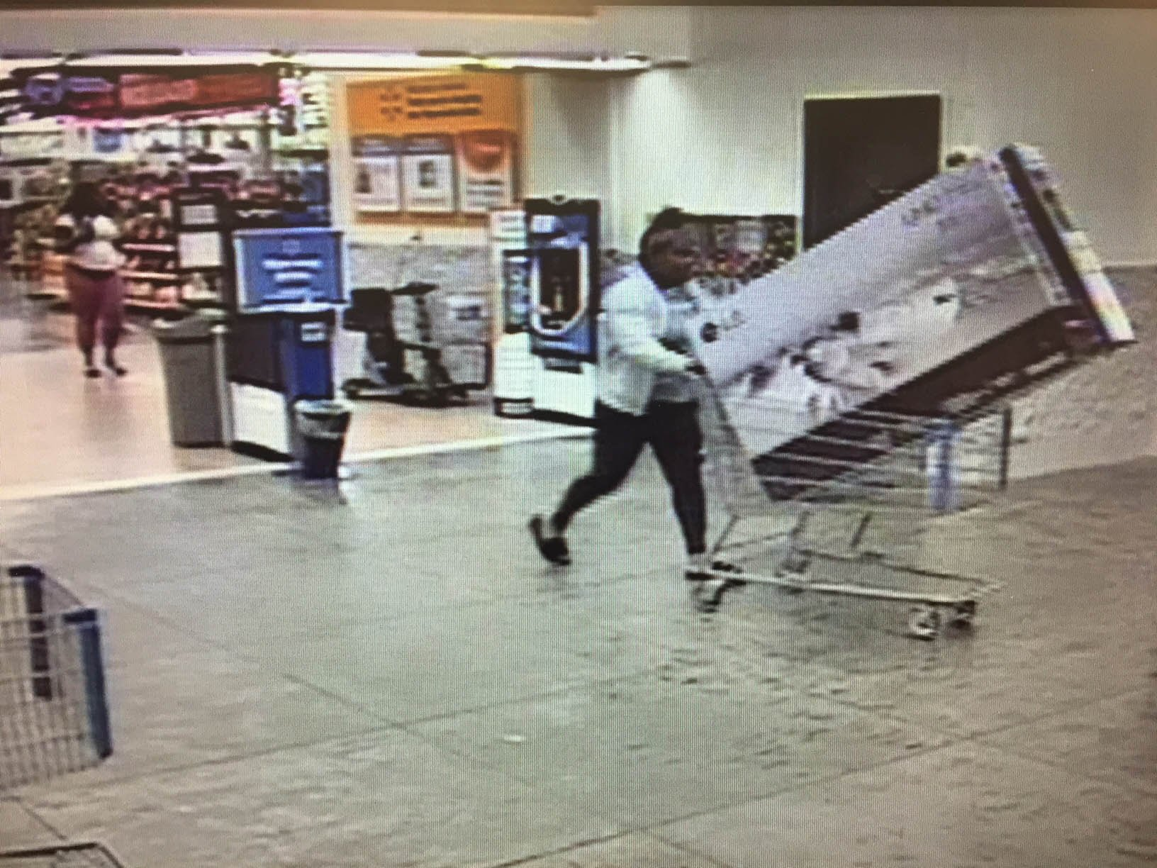 Surveillance Photo: Suspect leaving the store with both TVs
