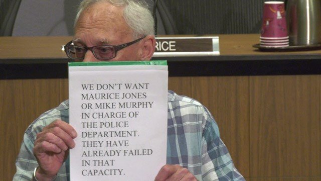 Jeffrey E. Fogel holding up a sign during an event for RaShall Brackney