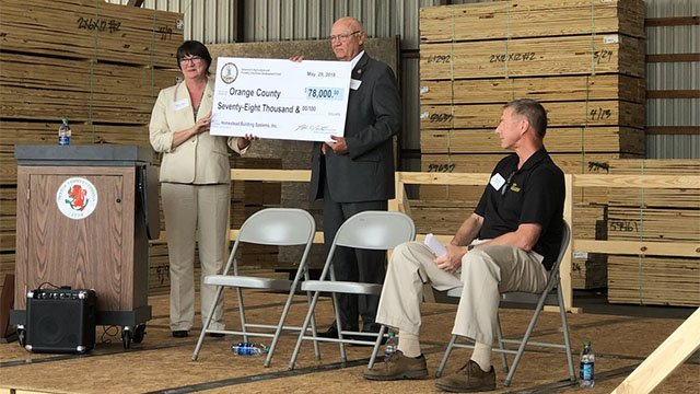 Secretary of Agriculture and Forestry presents Homestead Building Systems with a $78,000 check.