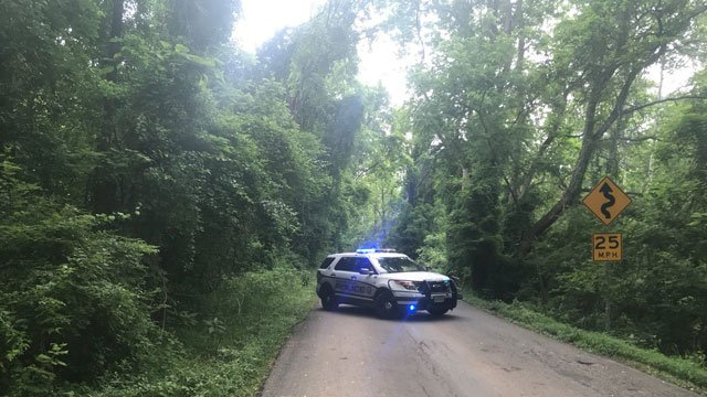 Police blocking a portion of Old Ballard Road, near where a body was found by search teams