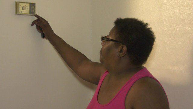 A resident of Crescent Halls shows her thermostat.