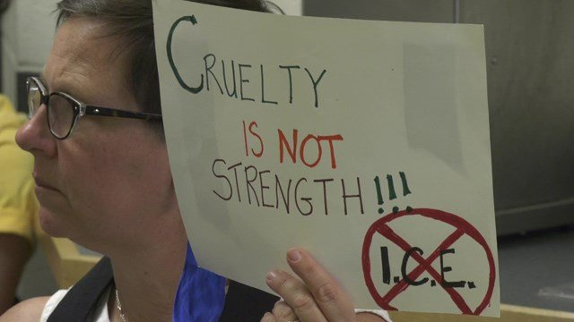 Woman holds sign in protest of ICE at ACRJ board meeting.