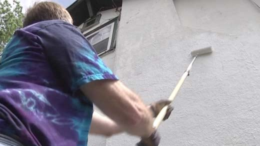 Volunteers help paint the side of a home