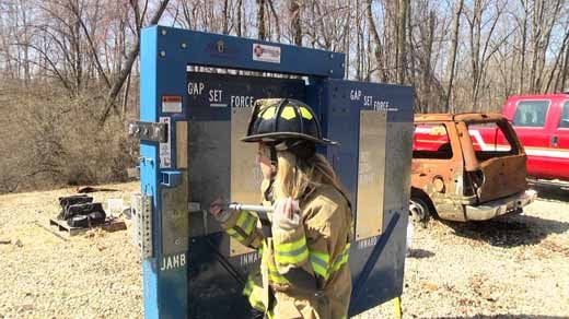 Cat Bordman steps into the shoes of firefighters in training. Bordman uses a halligan bar to open this door.