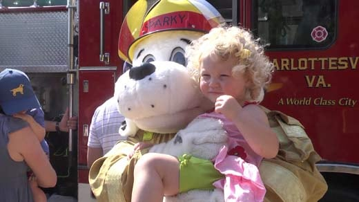A child is photographed with Sparky the Fire Dog.
