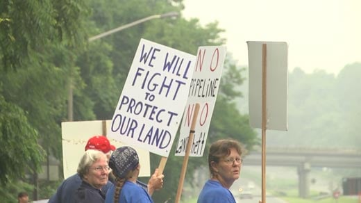 Protesters hold signs along Rt. 20 in hopes to get the attention of Governor Terry McAuliffe on his way to Monticello Saturday.