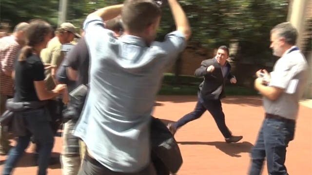 Jason Kessler running away from the crowd at a press conference (FILE IMAGE)
