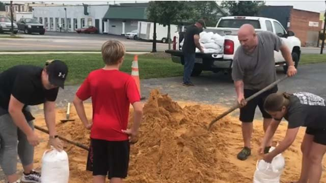 Families are filling sandbags to protect against flooding