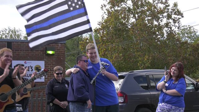 Ashton Ryan receiving a flag of support from local law enforcement