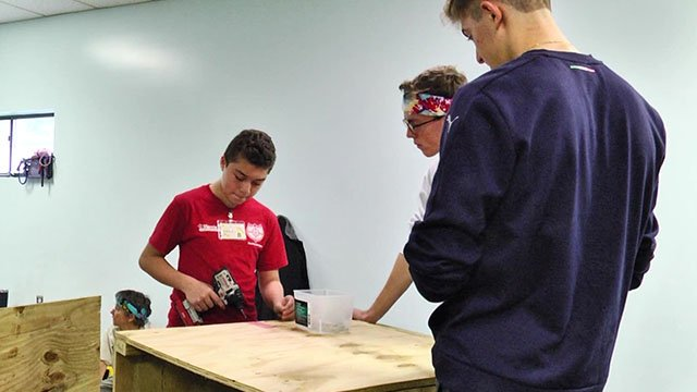 UVA student Christopher Sausa (right) and seventh grader Johan Numez (left) building a doghouse