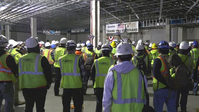 Workers pausing to honor military veterans