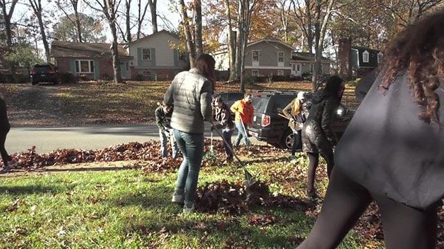 Volunteers raking a yard for a good cause