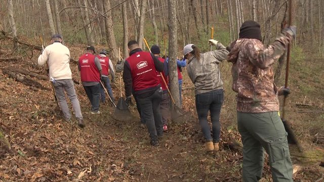 Volunteers from Lowe's work to clear a walking trail in the Southwood community.