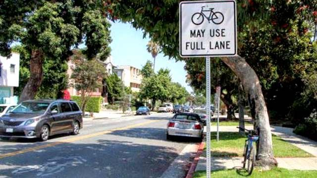 """""""Bikes May Use Full Lane"""" signs to protect bicyclists."""