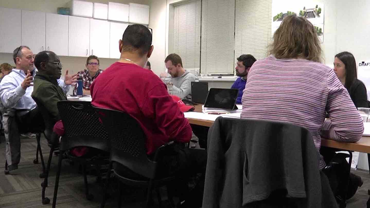 Members of the planning commission discussing city zoning.