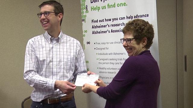 John Lukens receiving a check from the Alzheimer's Association